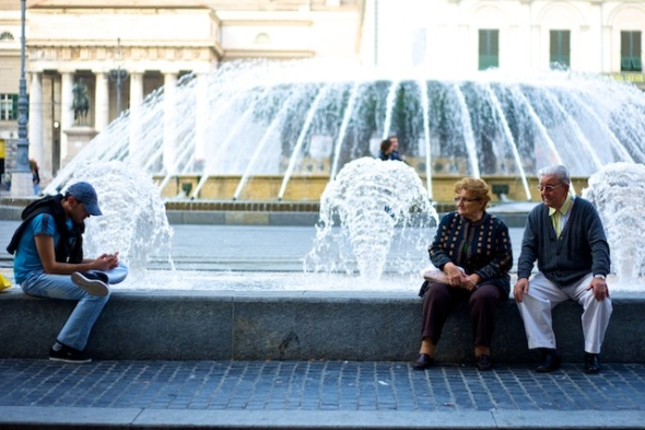 two elderly people in front of a fountain